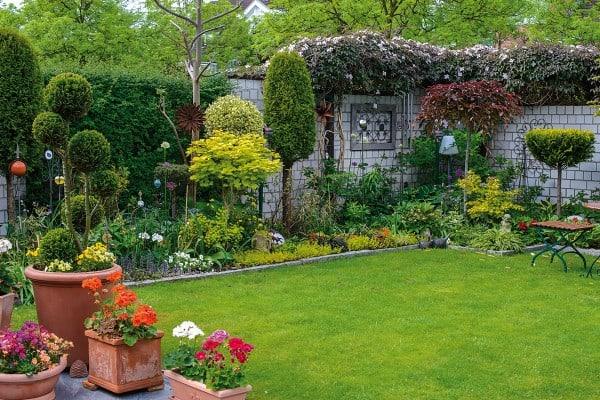 Добре поддържана градина с трева и цветя